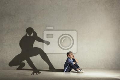 Fototapeta Ten malý chlapec sní o hrdinu se svaly. Koncepce dětství a snění. Konceptuální obraz s klukem a stínem vhodného sportovce na stěně studia