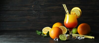 Fototapeta Tequila sunrise cocktail and ingredients on wooden table