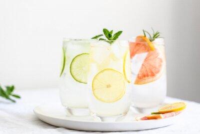 Fototapeta Three glasses with cold citrus lemonade with mint garnish on plate.