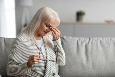 Fototapeta Tired mature woman rubbing dry irritated eyes