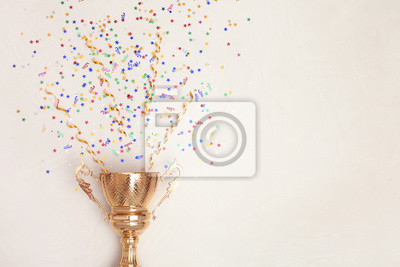 Fototapeta Trophy and confetti on light background, top view with space for text. Victory concept