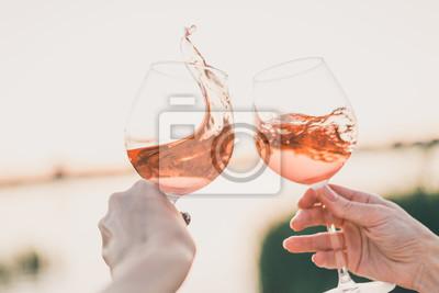Fototapeta Two glasses of rose wine in hands against the sunset sky.