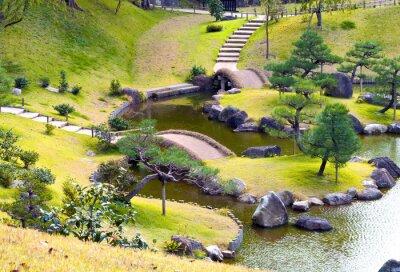 Fototapeta Upravená kopcovitý skalka s malými mosty přes vinutí potoka, do kopce kroky, borovic