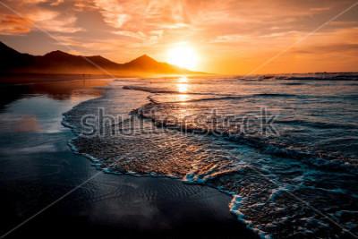 Fototapeta Úžasný západ slunce na pláži s nekonečným obzorem a osamělé postavy v dálce a neuvěřitelné pěnivé vlny. Vrcholné vulkanické kopce v pozadí v idylických, teplých barvách.