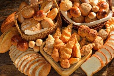 Fototapeta Variety chleba v proutěném koši na staré dřevěné pozadí.