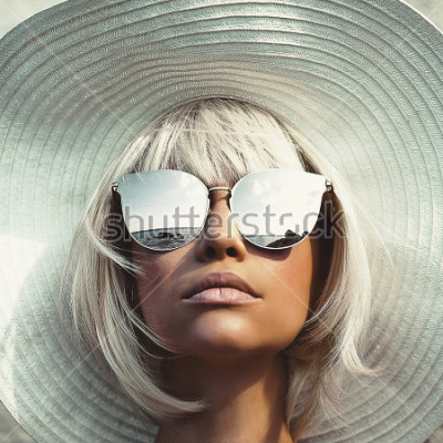 Fototapeta Venkovní módní fotografie mladé krásné dámy v klobouku a sluneční brýle. Letní pláž cestování. Letní vibrace
