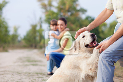 Cheerful friendly family and puppy are resting in park ...