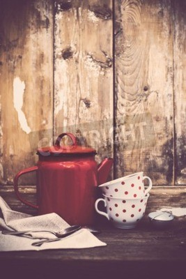 Fototapeta Vintage kuchyňské dekorace, červené smaltované kávové konvice a šálky s polka tečky na staré dřevěné desce pozadí s kopií prostoru. Rustikální domácí dekor.