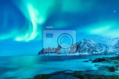 Fototapeta Vivid Northern lights during polar night on Lofoten Islands in Norway. Epic scene of dancing aurora borealis in the night sky over jagged mountain ridge and Arctic ocean on island Senja, polar circle.