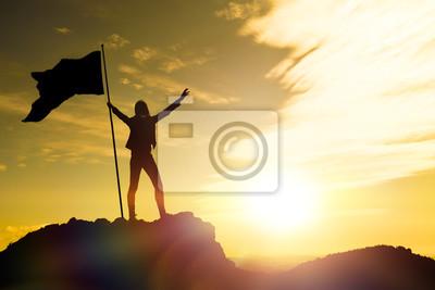 Fototapeta Vysoký výkon, siluety dívky, vlajka vítězství na vrcholu hory, ruce nahoru. Muž na vrcholu hory. Koncepční návrh. Proti dramatickému nebi s mraky při západu slunce.