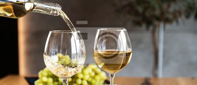 Fototapeta Waiter pouring white wine into wineglass.