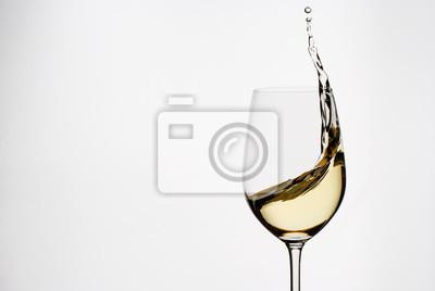 Fototapeta White wine splashing from an elegant wineglass