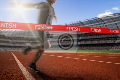 Fototapeta Winning young male Athlete crosses the finish line.