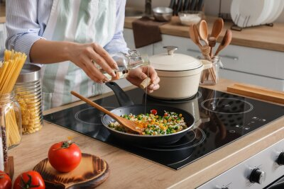 Fototapeta Woman cooking tasty rice with vegetables on stove in kitchen, closeup