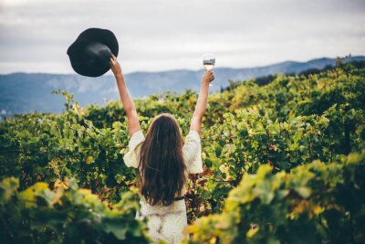 Fototapeta  Woman relaxing in the vineyards. Woman holding glass with white wine.