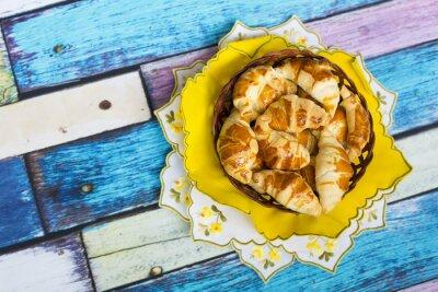 Fototapeta Самодельные круассаны в плетеной корзинке на желтой салфетке с цветочным узором на старом / вытертом полу