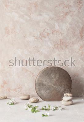 Fototapeta Zátiší s květinami, kameny a reliéfní keramickou vázou na texturovaném pozadí stěny ve stylu wabi-Sabi. Selektivní zaměření.