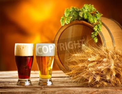 Fototapeta Zátiší složení s Vintage pivního sudu a dvě sklenice tmavé a světlé pivo. Čerstvé koncept jantarové pivo. Zelené kuří oka chmele a pšenice na dřevěném stole. Ingredience pro pivovary. Brewing traditi