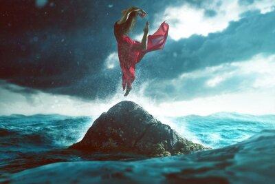 Fototapeta Žena tančí na skále v moři