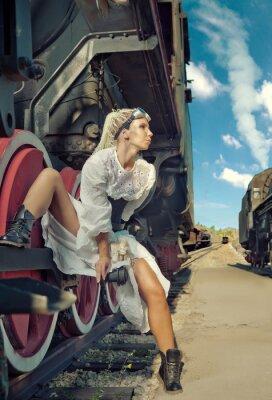 Fototapeta Žena ve vintage šaty sedí na kole lokomotivy.