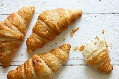 Fototapeta Zlaté croissanty na rustikální bílé dřevo, od shora.