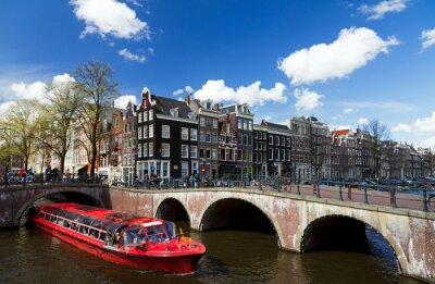 Nálepka Amsterdam kanál křižovatka s červeným výletní lodi v létě s modrou oblohou