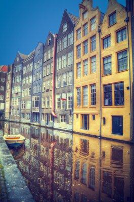 Nálepka Amsterdam na jaře. Domy jsou podél kanálů.