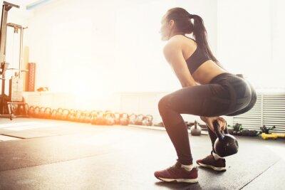Nálepka Atletická žena cvičení s bulina, přičemž je v dřepu pozici. Svalová žena, která dělá CrossFit cvičení v tělocvičně.