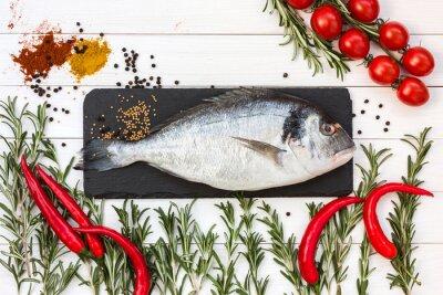 Nálepka Čerstvé ryby dorado, rozmarýn, cherry rajčata, chilli paprika na bílém dřevěném stole. Pohled shora.