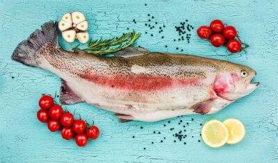 Nálepka Čerstvý pstruh ryby se zeleninou na modré dřevěný stůl. Pohled shora