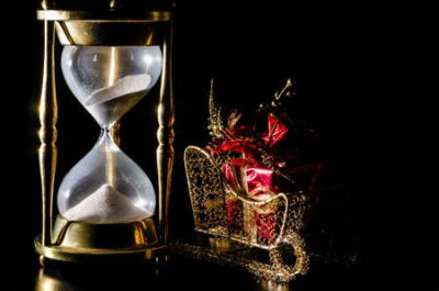 Christmas gift on sleigh and hourglass on black background   Concept showing time running out for Christmas shopping