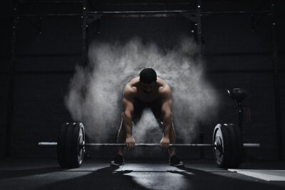 Nálepka Crossfit athlete preparing to lift heavy barbell in a cloud of dust at the gym. Barbell magnesia protection.