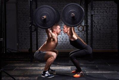 Nálepka Crossfit zvedání bar u ženy a muže ve skupině tréninku proti cihlové zdi.