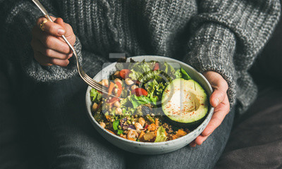 Nálepka Healthy vegetarian dinner. Woman in jeans and warm sweater holding bowl with fresh salad, avocado, grains, beans, roasted vegetables, close-up. Superfood, clean eating, vegan, dieting food concept
