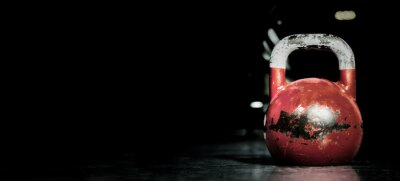 Nálepka Heavy old used color kettlebell weight on the gym floor ready for fitness strength workout to build muscles with dark background and free copy space banner