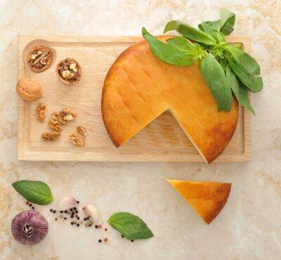 Nálepka Hlava uzeným sýrem Suluguni na dřevěné desce s ořechy a
