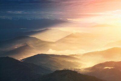 Nálepka Když v noci se stává den. Krásné kopce jasně osvětlené při východu slunce.