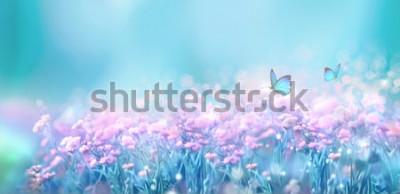Nálepka Květinová jarní přírodní krajina s divoce růžovými květy na louce a vlající motýly na pozadí modré oblohy. Zasněný jemný vzdušný umělecký obraz. Měkké zaostření, zpracování autorů.