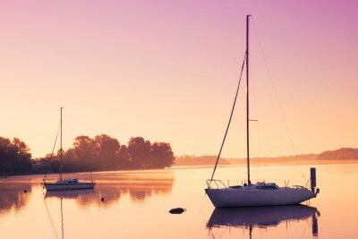 Nálepka Malé plachetnice odrážejí v klidné vodě při východu slunce.