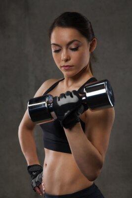 Nálepka Mladá žena protahování svalů s činkami v posilovně