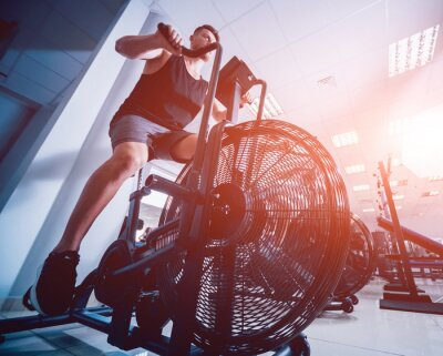 Nálepka Mladí muži s svalnaté tělo pomocí vzduchu kolo pro kardio cvičení v tělocvičně cross školení.