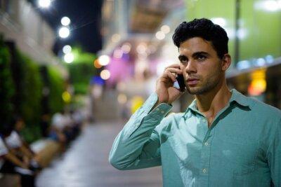 Nálepka Young handsome Hispanic man exploring the city streets at night