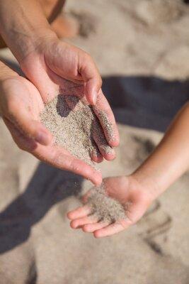 Písku protékající ženských rukou na dětském hands.Young žena s pískem v ruce si hraje s dítětem. Písek jako symbol pro čas krátí.