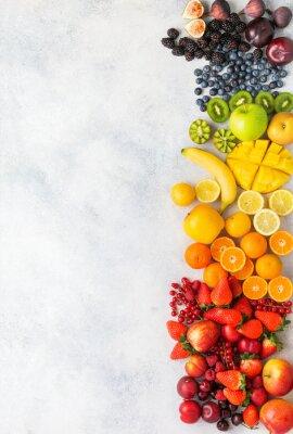 Nálepka Rainbow fruits berries background on white. Top view of strawberries blueberries cherries mango apple lemons oranges red currants plums blackberries, selective focus