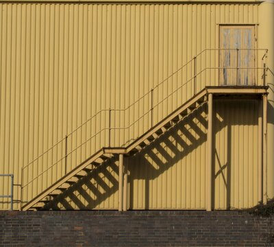Nálepka Schody vedoucí přes kovový sidinf zdi.