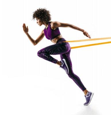 Nálepka Silná dívka v siluetě pomocí odporového pásma. Fotografie mladé africké dívky provádí fitness cvičení izolovaných na bílém pozadí. Boční pohled