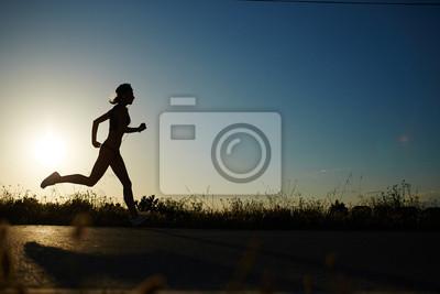 Nálepka Silueta sportovní holka běží po silnici k západu slunce