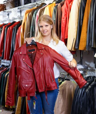 Nálepka Smiling female customer satisfied with purchases in leather clothing boutique