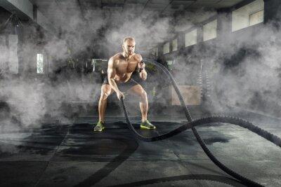 Nálepka Sportovní mladý muž s bitevní lano dělá cvičení ve fitness tělocvičně. Sportovní koncept.