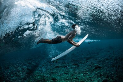 Nálepka Surfer performs dive (the duck dive) with his surfboard under the wave and exhales air into the water.